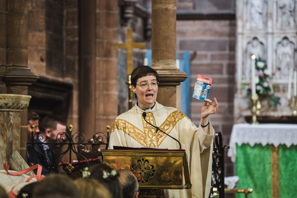 vicar during wedding ceremony at exchanging vows at St. Bartholomew's Thurstaston england