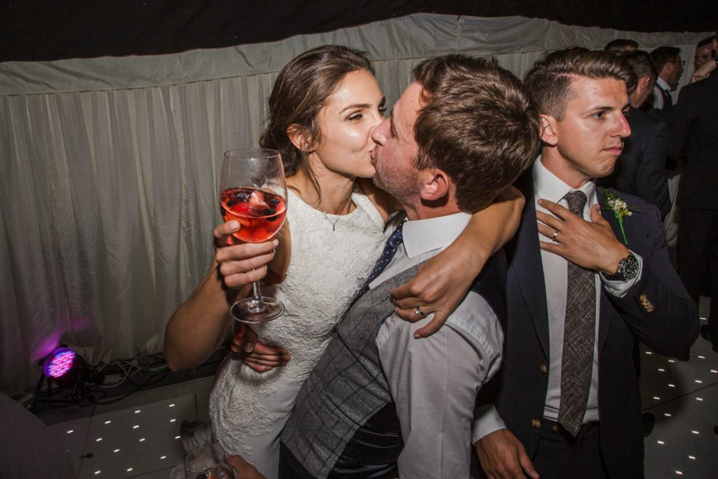 bride and groom kiss at the party